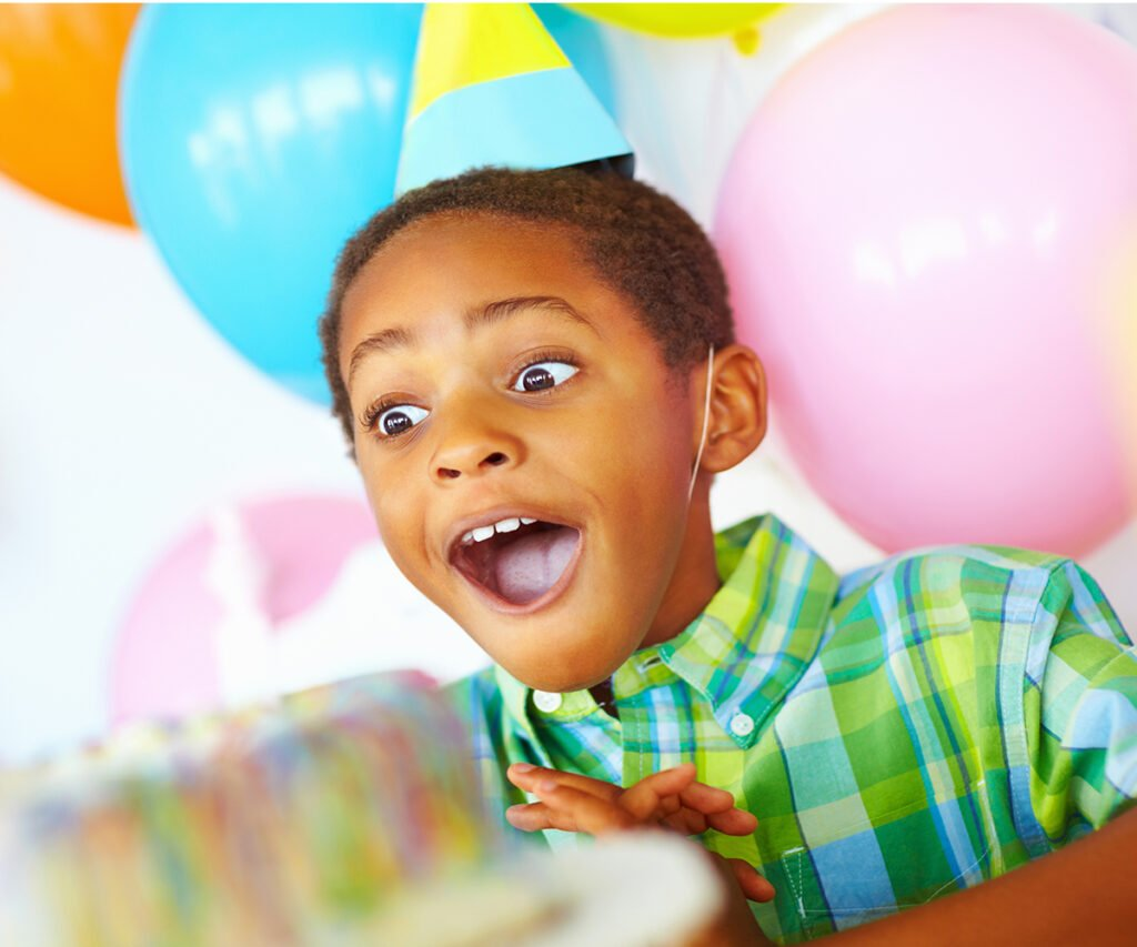 African American kid with a surprise expression looking at cake