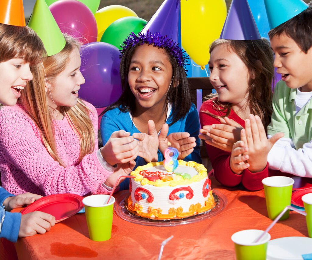 Multi-ethnic children (7-10 years) having fun at birthday party. Lit candle (number 8) on the cake.